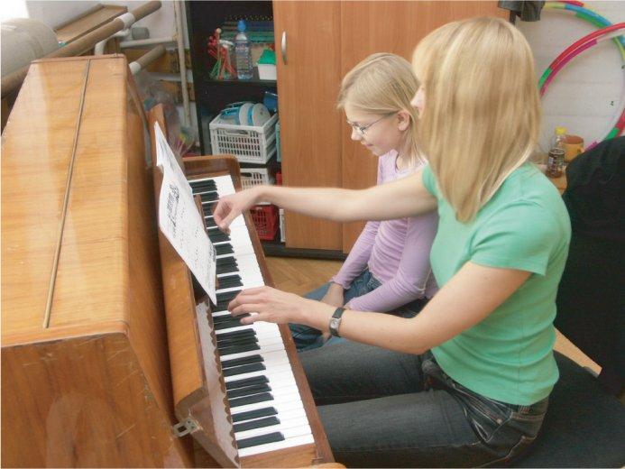 Dziewczynka i prowadząca przy pianinie