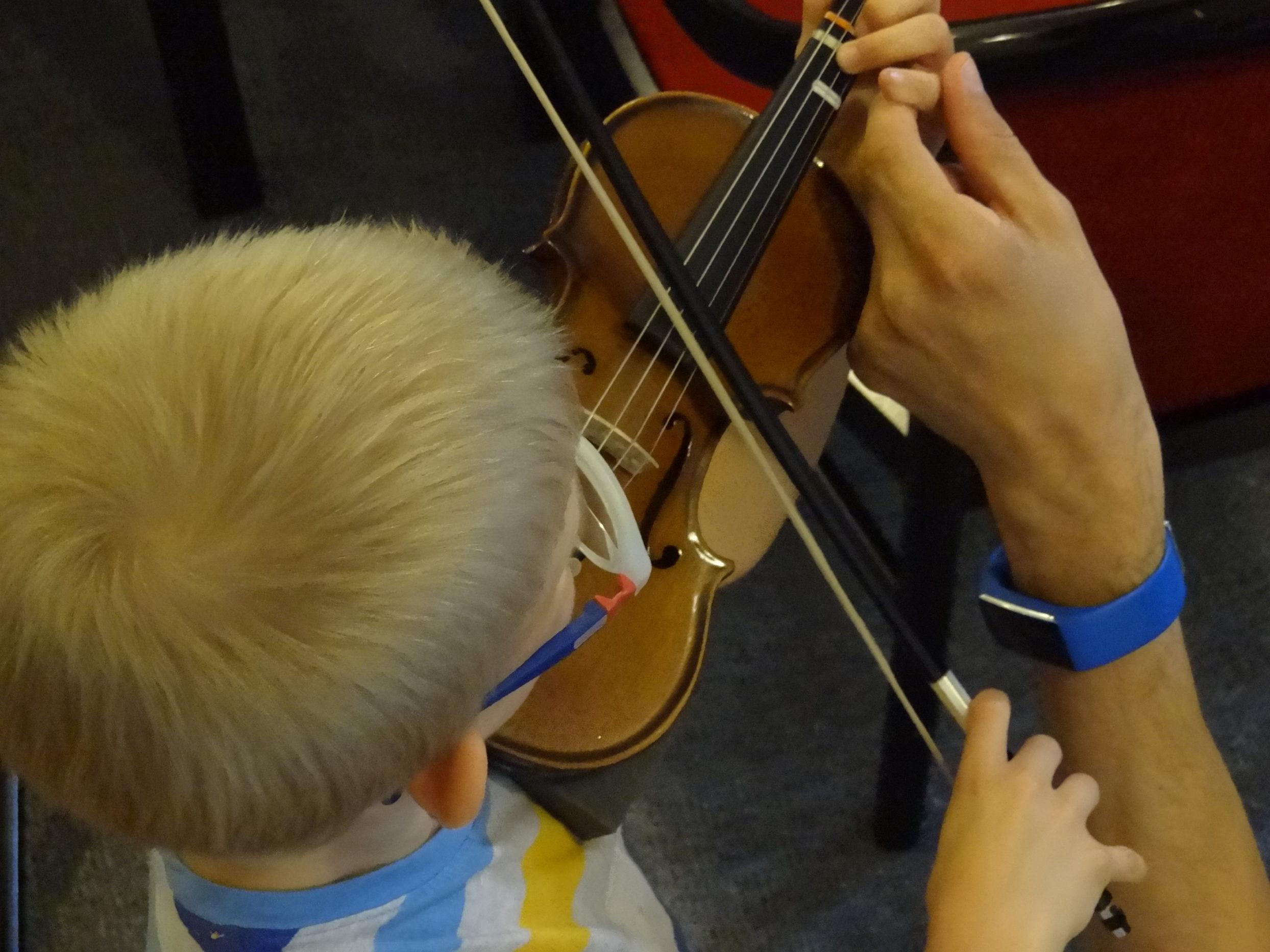 chłopiec ćwiczy grę na skrzypcach