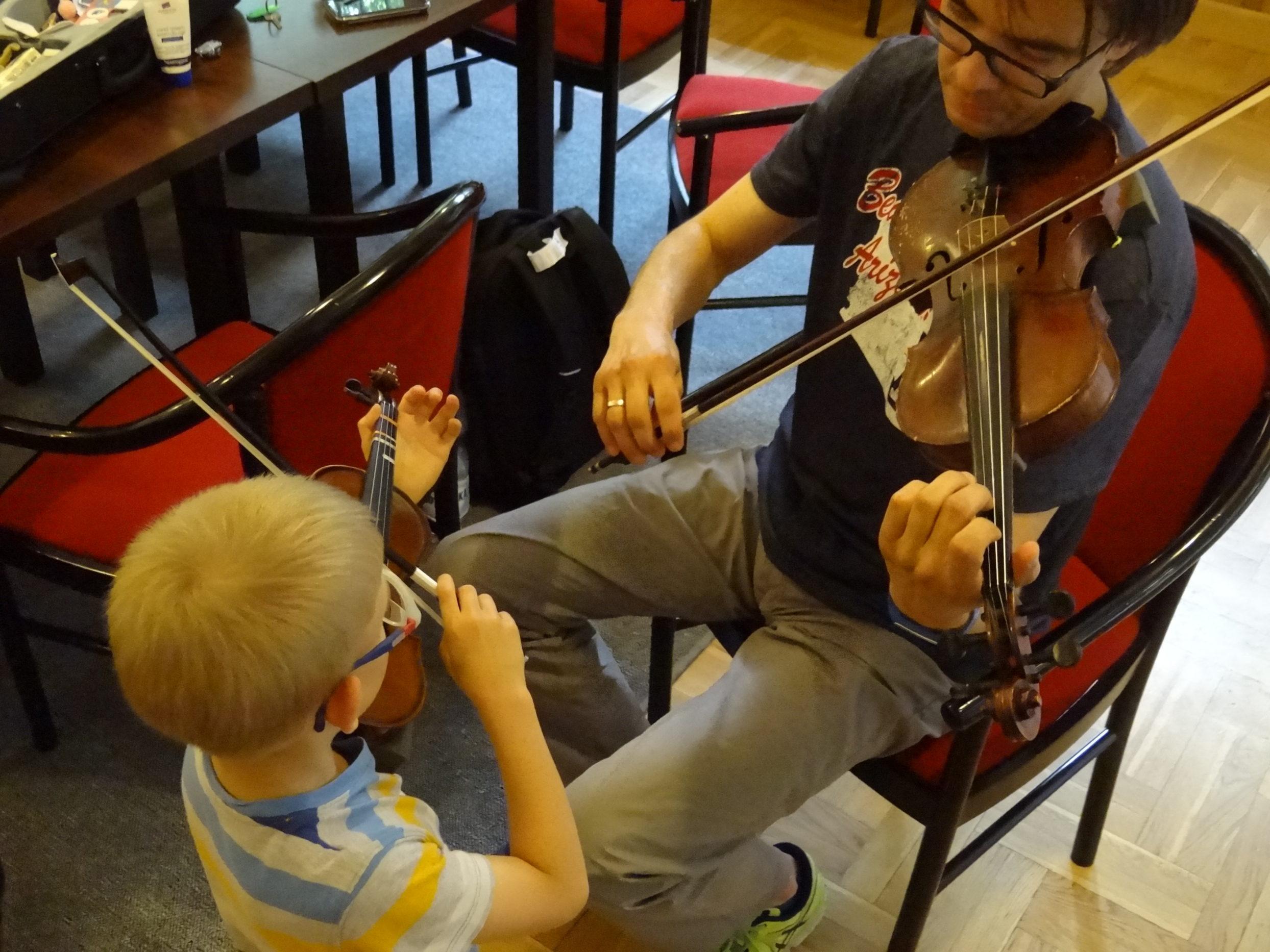uczeń i nauczyciel wspólnie grają na skrzypcach