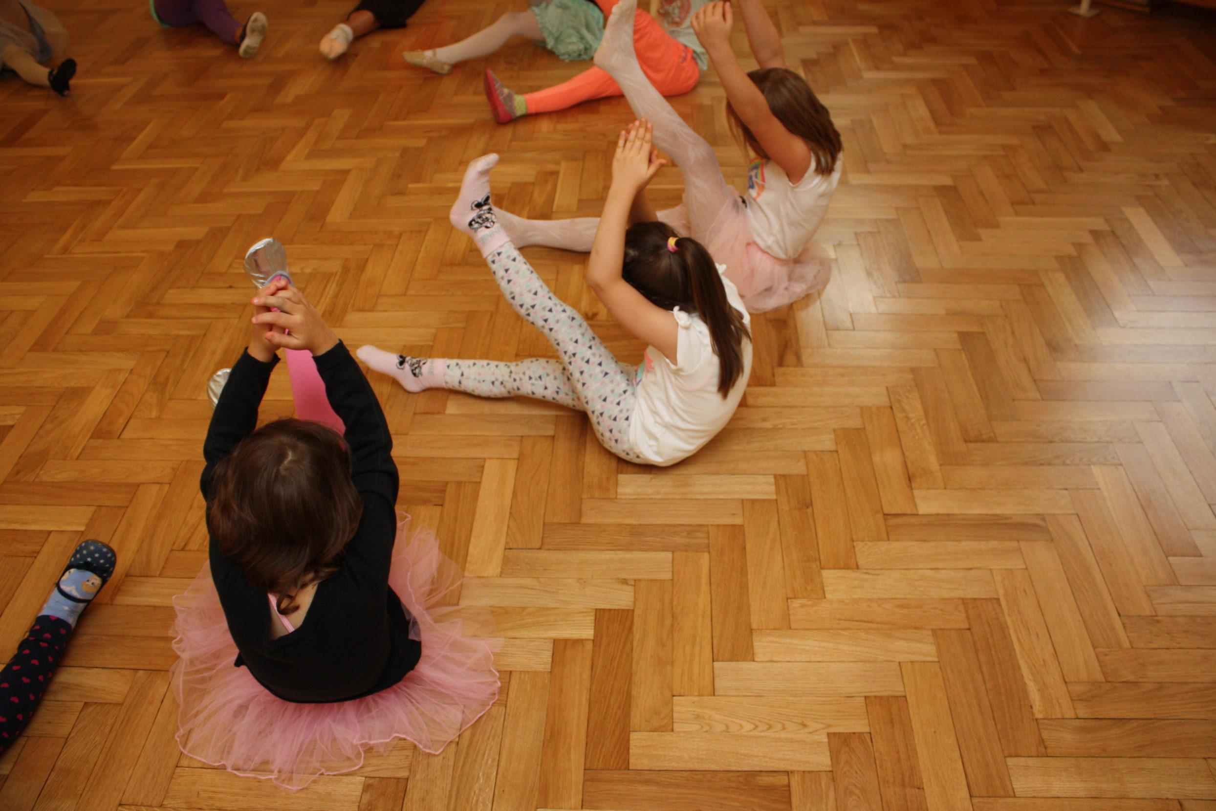 Dziewczynki w strojach baletowych siedzą na podłodze w trakcie rozgrzewki