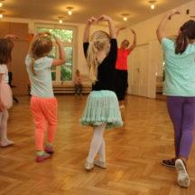 Dziewczynki wykonujące figurę baletową z rękoma w górze