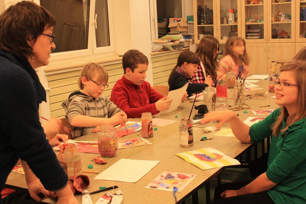 Dzieci w czasie zajęć plastycznych słuchające prowadzącej zajęcia