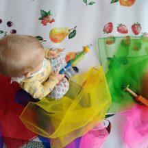 małe dziecko siedzące na kolorwej ceracie z drewnianą zabawką