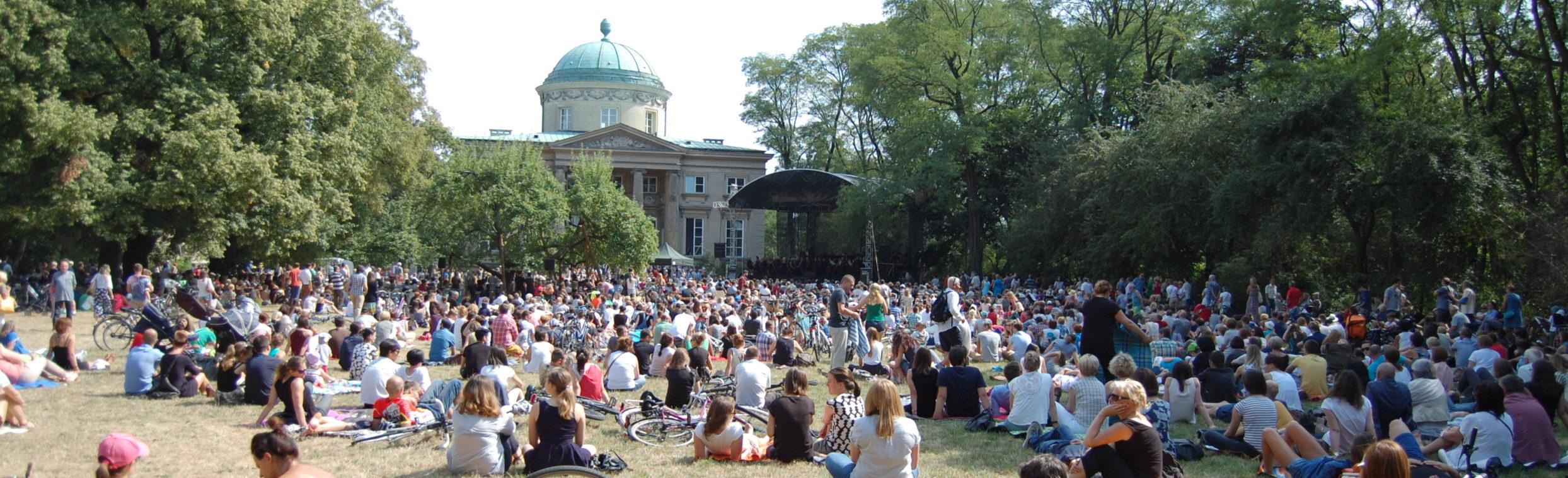Publiczność na trawie słuchająca koncertu