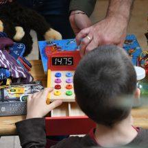 zdjęcie z wyprzedaży garażowej, na nim głowa dziecka, drewniana kasa i inne przedmioty