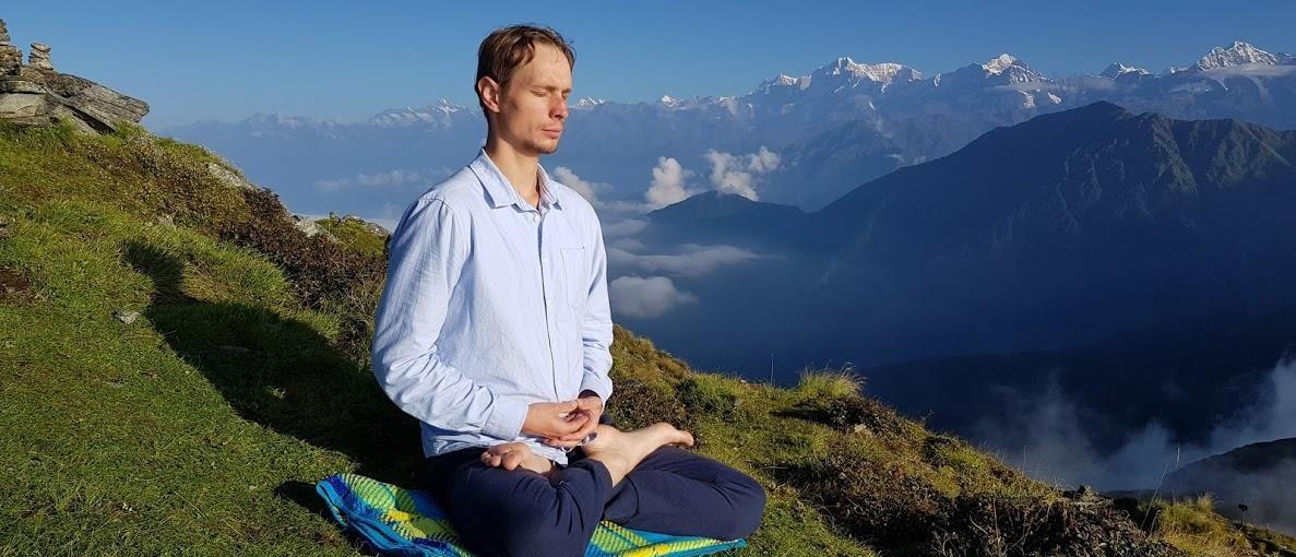 mezczyzna medytujacy na tle gór