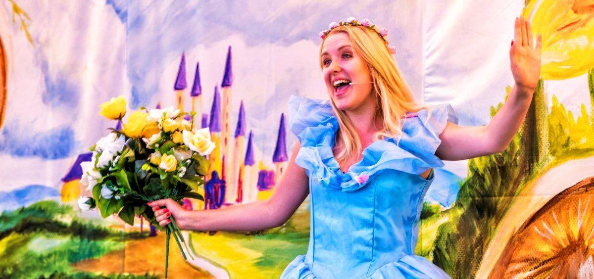 aktorka- ksiezniczka, w niebieskiej sukience z bukietem żółtych róż