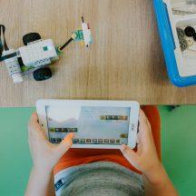 dłonie dziecka z tabletem, robot na stole